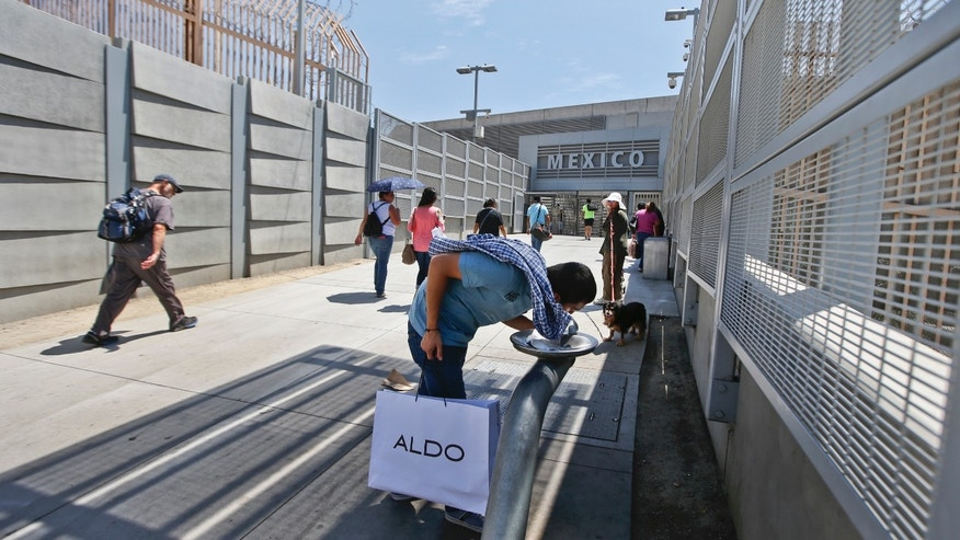 In this Tuesday, Aug. 18, 2015, photo, a man headed into Mexico stops at a fountain as fellow travelers approach the entrance to the Mexico border crossing in San Ysidro, Calif. Starting late Wednesday, Aug. 19, pedestrians going to Tijuana from San Diego at the San Ysidro crossing must choose between a line for Mexicans who get waved through, and a line for foreigners. Foreigners must show a passport, fill out a form and - if staying more than a week - pay for a six-month permit. (AP Photo/Lenny Ignelzi)
