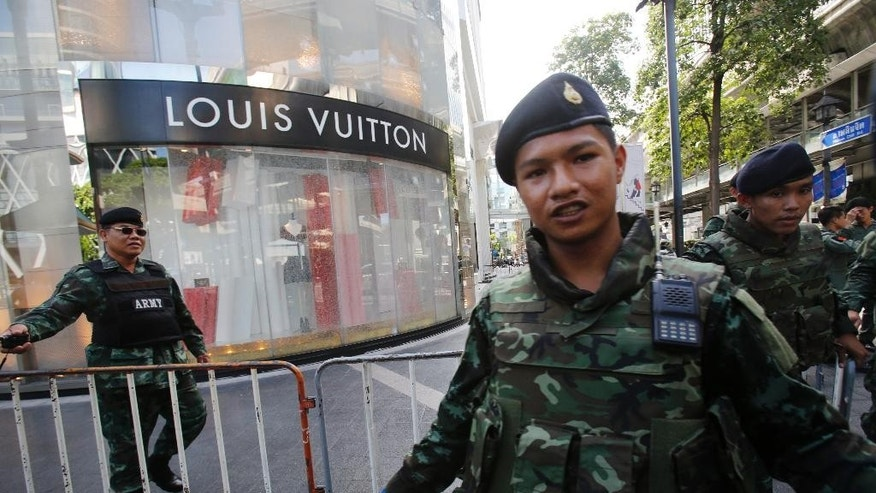 In this Aug. 18, 2015, photo, soldiers move onlookers back from the shattered windows of a Louis Vuitton shop at Gaysorn shopping plaza across from the Erawan Shrine at Rajprasong intersection after a bombing in Bangkok, Thailand. In Bangkok this week, struggling in the aftermath of an unexplained bombing that left 20 people dead and more than 120 injured, the explosion made starkly clear that cities are still wrestling with the question: How do we keep ourselves safe? (AP Photo/Sakchai Lalit)
