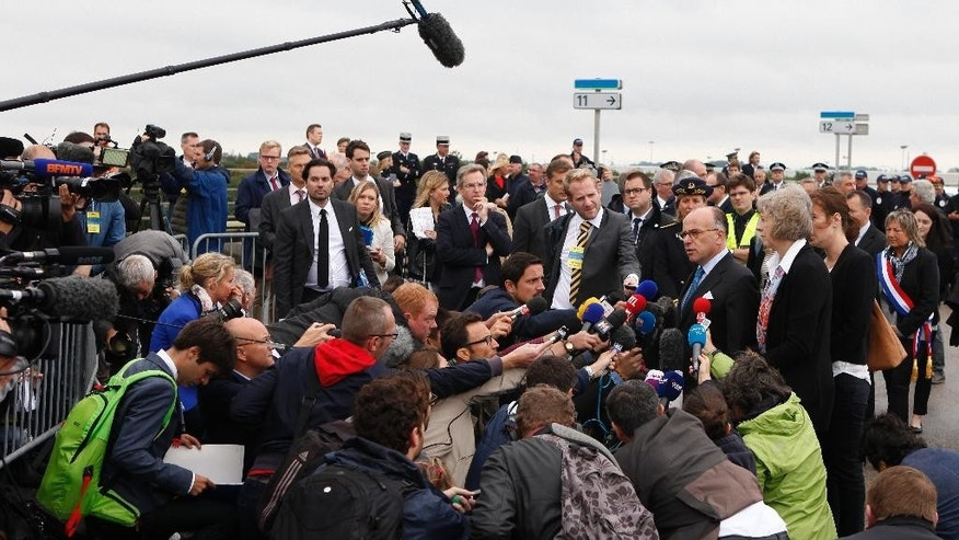French Interior Minister Bernard Cazeneuve and Britain's Britain Home Secretary Theresa May answer journalists after their arrival at the at the Eurotunnel entrance, in Calais, northern France,Thursday, Aug. 20, 2015. Britain and France are fortifying control of the Channel Tunnel and boosting intelligence efforts against traffickers as they try to dissuade thousands of migrants trying to make the illegal _ and sometimes deadly _ undersea journey to British shores. (AP Photo/Michel Spingler)