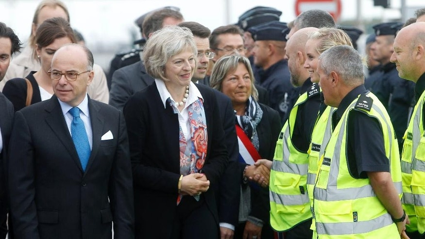 French Interior Minister Bernard Cazeneuve, left, and Britain's Britain Home Secretary Theresa May meet British police officers, right, at the Eurotunnel entrance, in Calais, northern France,Thursday, Aug. 20, 2015. Britain and France are fortifying control of the Channel Tunnel and boosting intelligence efforts against traffickers as they try to dissuade thousands of migrants trying to make the illegal _ and sometimes deadly _ undersea journey to British shores. (AP Photo/Michel Spingler)