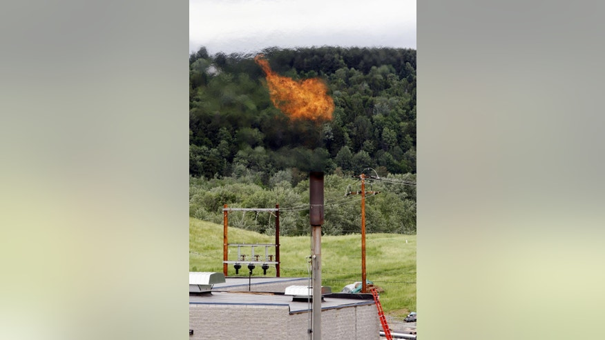 FILE - In this June 15, 2005 photo, methane gas burns off a stack near the Washington Electric Cooperative power plant in Coventry, Vt.  The Obama administration is proposing to cut methane emissions from U.S. oil and gas production by nearly half over the next decade in an unprecedented step to curb climate change. (AP Photo/Toby Talbot, File)