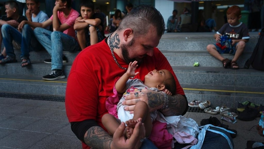 In this Thursday, Aug. 13, 2015, photo, volunteer Baba Mujhse holds a newly-arrived migrant baby in front of the Keleti railway station in Budapest, Hungary. Mujhse is 6-foot-6, built like an NFL linebacker and has tattoos all over his body. Baba Mujhse may sound like the type of guy most people would run away from, but hundreds of desperate migrants are instead running to him for help. (AP Photo/Bela Szandelszky)