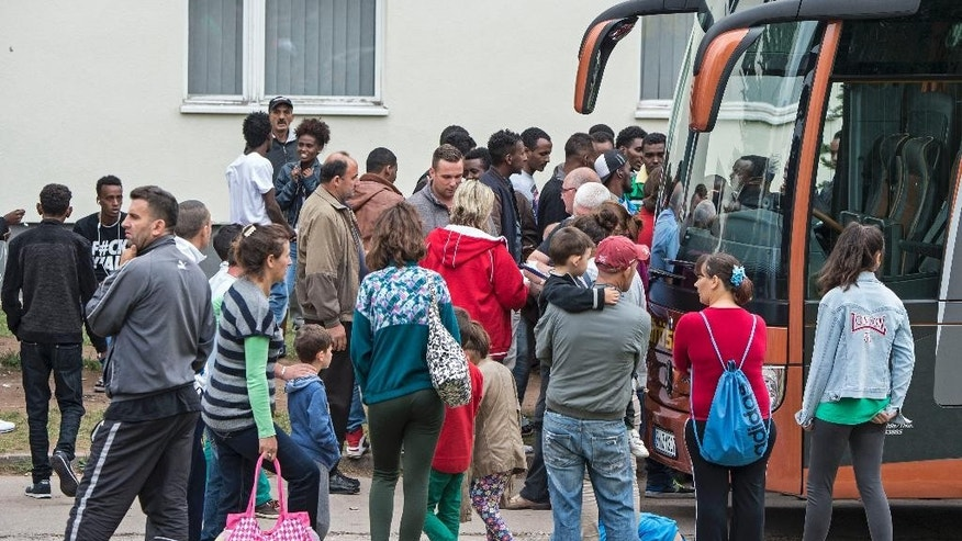 Refugees wait in front of a bus t a  refugee home  in Suhl, central Germany, Thursday, Aug. 20, 2015. Police say they are investigating a clash at the  asylum-seekers' home in which 11 refugees and three police officers were injured late Wednesday. Police say some 50 residents were involved and as many more watched the clash.  (AP Photo/Jens Meyer)