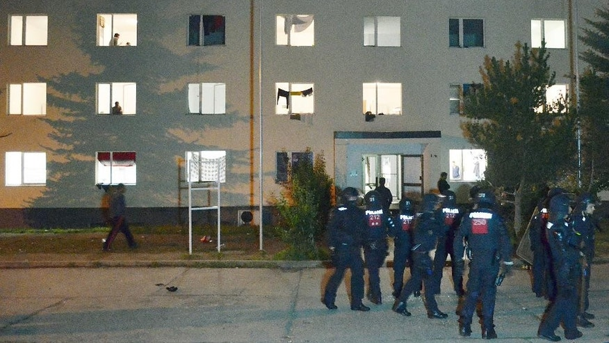 Police officers stand in front of the asylum-seekers home  in Suhl, Germany,Thursday morning  Aug. 20, 2015 .Police say they are investigating a clash at the  asylum-seekers' home in which 11 refugees and three police officers were injured late Wednesday. Police say some 50 residents were involved and as many more watched the clash. ( Martin Wichmann/dpa via AP)