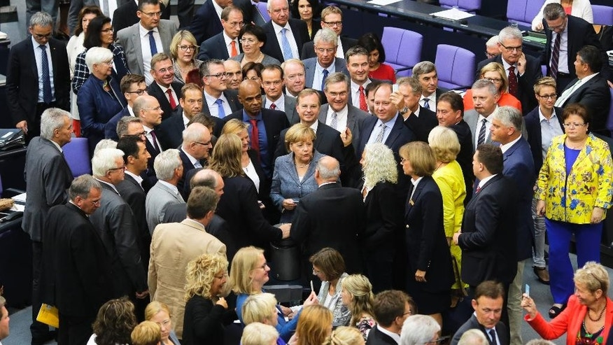 German Chancellor Angela Merkel, center, stands between lawmakers after she casts her vote on a bailout package for Greece, in the German parliament Bundestag in Berlin, Wednesday, Aug. 19, 2015. (AP Photo/Markus Schreiber).