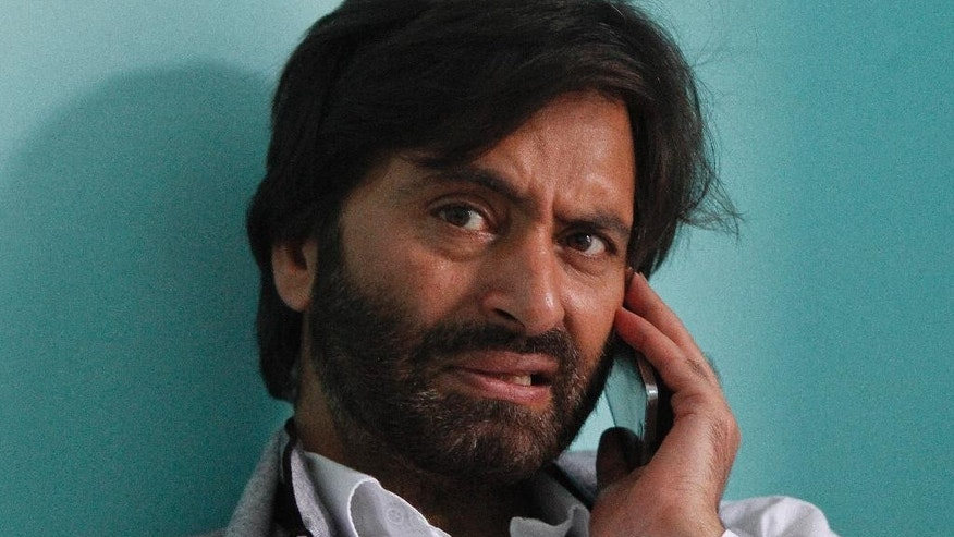 Kashmiri separatist leader Mohammed Yasin Malik receives a phone call inside his office after he was released by Indian authorities in Srinagar, Indian-controlled Kashmir, Thursday, Aug 20, 2015. Indian authorities detained and later released two key Kashmiri separatist leaders ahead of talks between Indian and Pakistani security advisers. A third leader is under house arrest.(AP Photo/Mukhtar Khan)