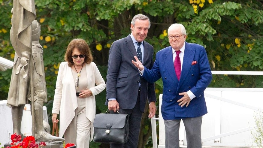 Jean-Marie le Pen, right, former head of far-right party National Front, his lawyer Frederic Joachim and his wife Jany arrive at the party headquarters in Nanterre, outside Paris, France, Thursday, Aug 20, 2015.  Le Pen risks suspension or exclusion from the far-right National Front he helped found more than four decades ago in a new effort by his daughter, the president, to oust him.  At left is a statue of Joan of Arc. (AP Photo/Jacques Brinon)