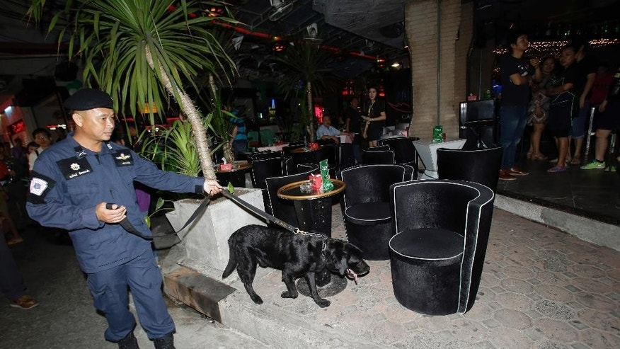 A Thai policeman patrols with a bomb sniffing dog in Bangkok, Thailand. Thursday, Aug. 20, 2015. Three days after the attack at a revered shrine in central Bangkok killed 20 people, authorities appeared to have few solid leads into the perpetrators of the deadliest attack in Thailand's recent history. Police said they suspect the plot involved at least 10 people but described that figure as theoretical. (AP Photo/Sakchai Lalit)