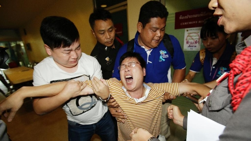 Gao Yan Ping, from Jiangxi province, China, center, is overcome with emotion at the Police General Hospital in Bangkok, Thailand, after he arrived to claim the body and remains of his daughter and his wife who were killed in Monday's bombing at the Erawan Shrine, Thursday, Aug. 20, 2015. (AP Photo/Sakchai Lalit)