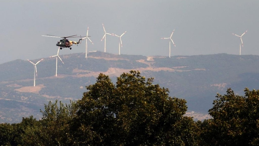 A police helicopter flies near the border between Greece and Macedonia, near the southern Macedonian town of Gevgelija, Thursday, Aug. 20, 2015. Macedonian  police  stepped up the security at the border with Greece apparently trying to stem recent surge of migrants who are coming from Greece. (AP Photo/Darko Vojinovic)