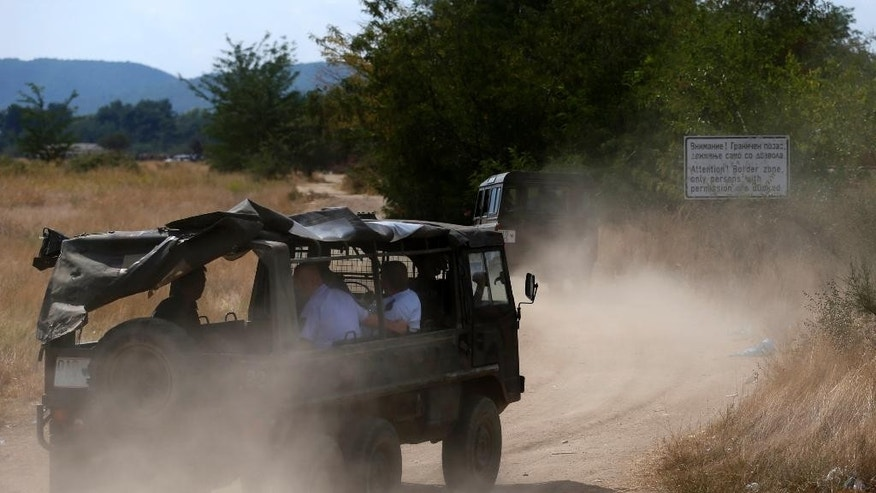 Police vehicles drive to the border between Greece and Macedonia, near the southern Macedonian town of Gevgelija, Thursday, Aug. 20, 2015. Macedonian  police  stepped up the security at the border with Greece apparently trying to stem recent surge of migrants who are coming from Greece. (AP Photo/Darko Vojinovic)