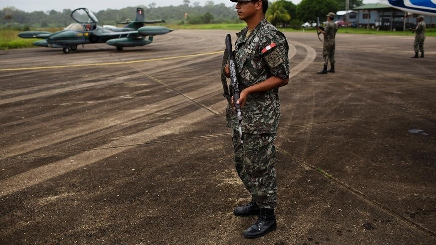FILE - In this June 2, 2015, file photo, soldiers stand guard at a military base in Madre de Dios, Peru. Peru's Congress has unanimously approved legislation on Thursday, Aug. 20, 2015, authorizing military planes to shoot down suspected drug flights, which police say smuggle more than a ton of cocaine to Bolivia daily. (AP Photo/Rodrigo Abd, File)