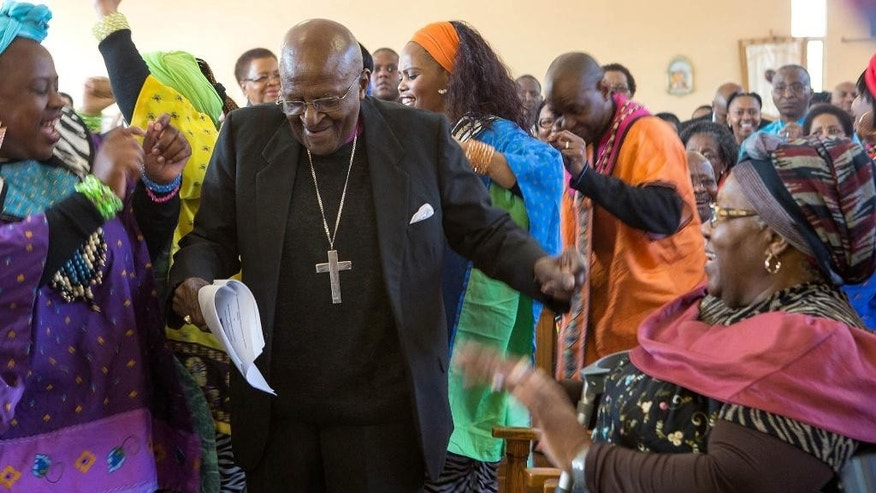 FILE - In this Saturday, July 4, 2015 file photo, retired Anglican Archbishop Desmond Tutu, center, breaks into dance after renewing his wedding vows to his wife of 60 years, Leah, right, during a service in Soweto, Johannesburg. A South African foundation says retired archbishop Desmond Tutu will have to spend two more weeks in hospital, after being hospitalized for the third time in nearly two months.  The foundation, which is named after Tutu and his wife Leah, said on Thursday, Aug. 20, 2015 the anti-apartheid activist is on a new course of intensive antibiotic treatment. (AP Photo, File)