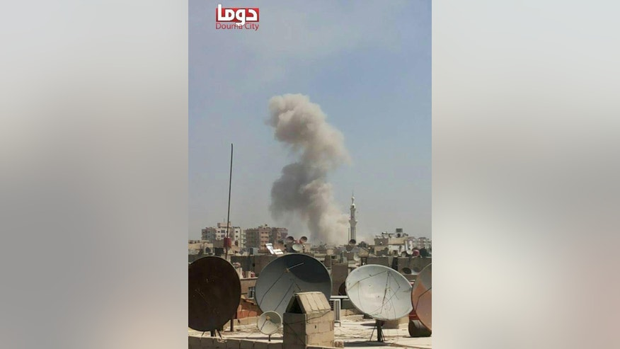 This photo provided by the Syrian anti-government activist group Douma Revolution, which has been authenticated based on its contents and other AP reporting, shows smoke arise from a Syrian government airstrike, in Douma, a suburb of Damascus, Syria, Thursday, Aug. 20, 2015. An international human rights group called on the U.N. Security Council to impose an arms embargo on the Syrian government following airstrikes on a rebel-held suburb that killed more than 100 people. Many of those killed in the Aug. 16 attacks that targeted Douma's popular markets and residential areas were civilians. The New York-based Human Rights Watch said in a press release that the U.N. should also refer the situation in Syria to the International Criminal Court.(Douma Revolution via AP)