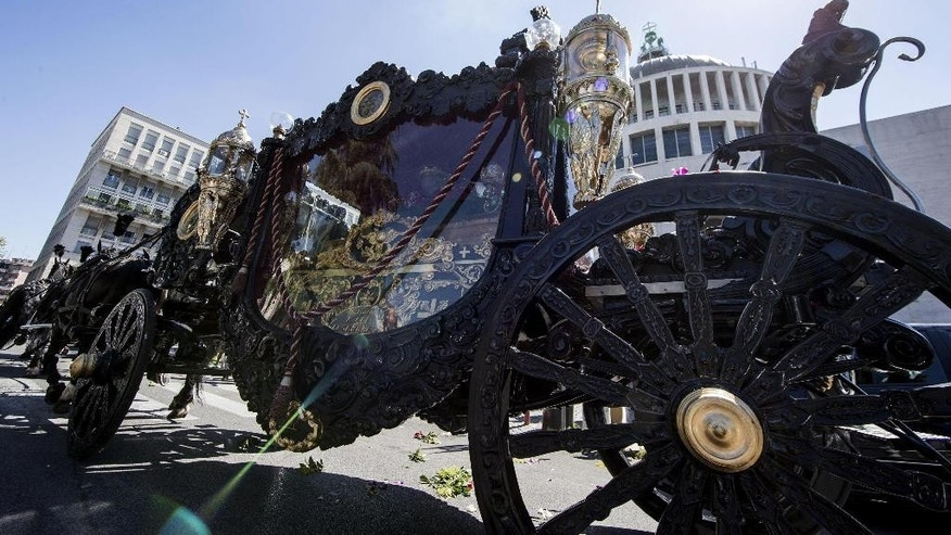 "A horse-drawn carriage containing the coffin of purported mafia boss Vittorio Casamonica is driven past the Don Bosco church during the funeral ceremony in Rome, Thursday, Aug. 20, 2015. Romans aghast at spiraling mafia probe have found new reason for alarm after witnessing the Hollywood-style funeral of a purported mafia boss, complete with a horse-drawn carriage, flower petals tossed from a helicopter and the theme music from ""The Godfather"" playing. (Massimo Percossi/ANSA via AP)"