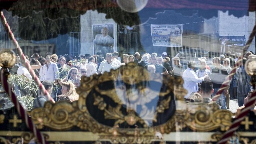 "Mourners are seen through an horse-drawn carriage containing the coffin of purported mafia boss Vittorio Casamonica, during the funeral ceremony in Rome, Thursday, Aug. 20, 2015. Romans aghast at spiraling mafia probe have found new reason for alarm after witnessing the Hollywood-style funeral of a purported mafia boss, complete with a horse-drawn carriage, flower petals tossed from a helicopter and the theme music from ""The Godfather"" playing. (Massimo Percossi/ANSA via AP)"