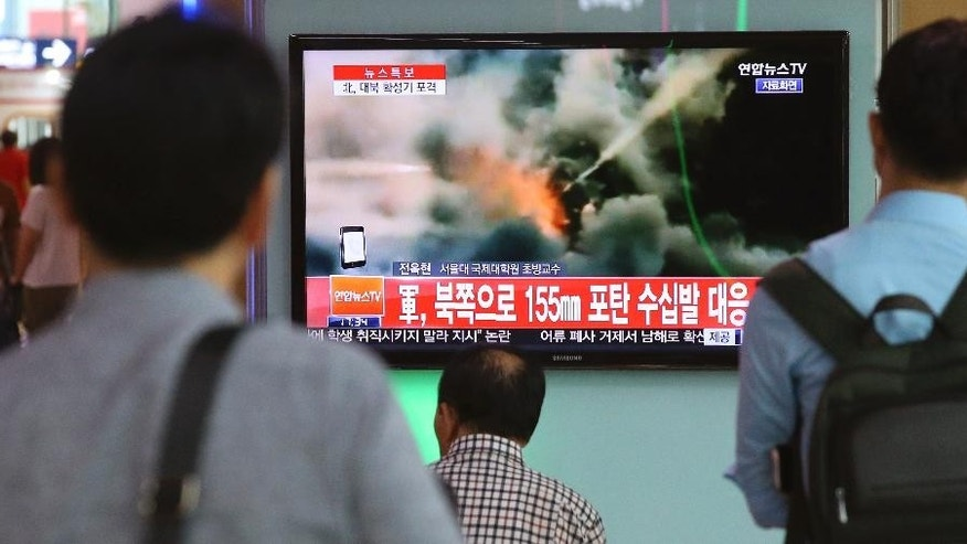 "People watch a television news program reporting about South Korea's respond to the North with a file video footage at Seoul train station in Seoul, South Korea, Thursday, Aug. 20, 2015. South Korea's military fired dozens of shells Thursday at rival North Korea after the North lobbed a single artillery round at a South Korean border town, the South's Defense ministry said. The letters read ""South Korean military, respond 155mm shells to the North."" (Kim Do-hun/Yonhap via AP) KOREA OUT"