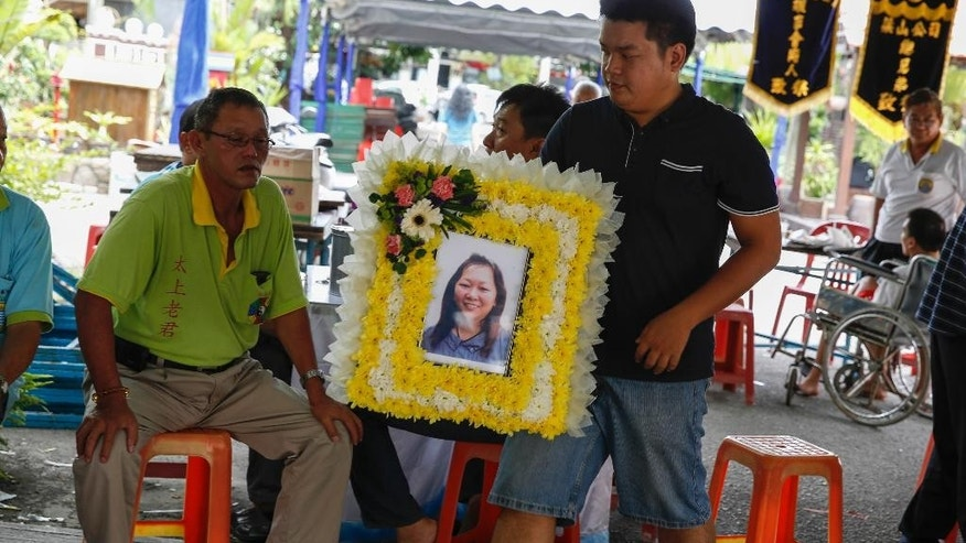 A relative of Lim Saw Gek, a victim of the recent Bangkok bombing, carries her portrait for the wake ceremony at the Neoh's house in Penang, Malaysia, Thursday, Aug. 20, 2015. Lim was killed in Monday's deadly bombing in central Bangkok. (AP Photo/Joshua Paul)