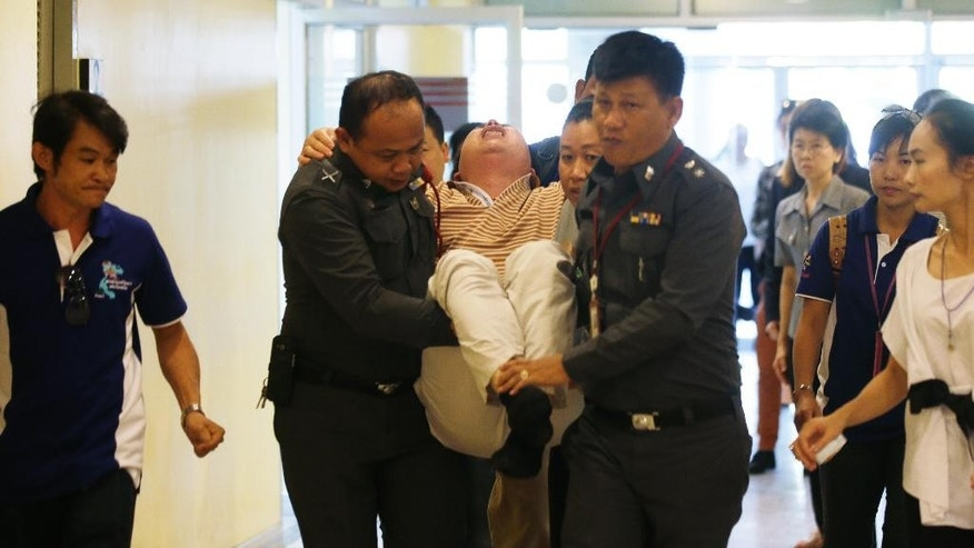 Gao Yan Ping, from Jiangxi province, China, center, is carried by police officers as he is overcome with emotion at the Police General Hospital in Bangkok, Thailand, after he arrived to claim the body and remains of his daughter and his wife who were killed in Monday's bombing at the Erawan Shrine, Thursday, Aug. 20, 2015. (AP Photo/Sakchai Lalit)