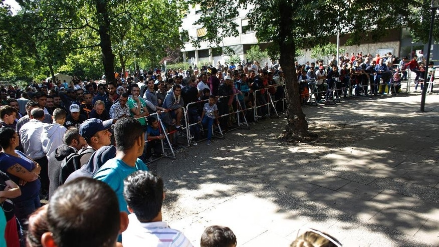 Hundreds of migrants wait outside of the reception center for refugees and asylum-seekers in Berlin, Friday, Aug. 21, 2015. (AP Photo/Markus Schreiber).