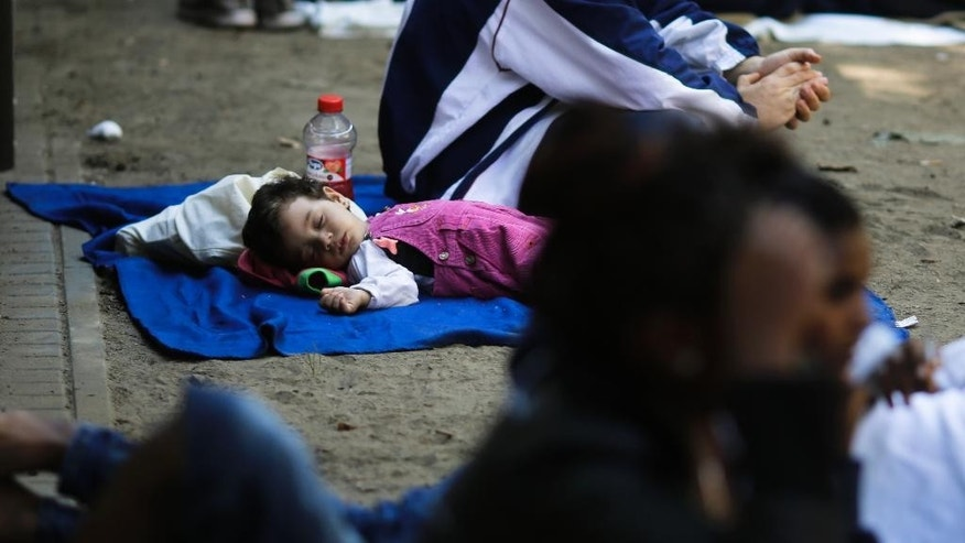 A refugee child from Palestine sleeps next to its father outside  the reception center for refugees and asylum-seekers in Berlin, Friday, Aug. 21, 2015. (AP Photo/Markus Schreiber).