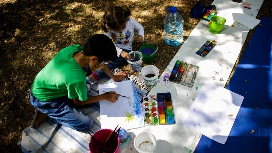 Migrant children paint pictures at the area outside the reception center for refugees and asylum seekers in Berlin, Friday, Aug. 21, 2015. A honorary citizens' initiative offers activities for children during the time the parents line up for their registration. (AP Photo/Markus Schreiber).