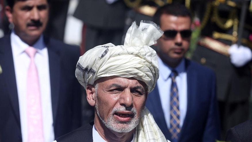 """In this Wednesday, Aug. 19, 2015 photo, Afghanistan President Ashraf Ghani sings the national anthem after putting flowers on the """"Independence Minaret"""" monument during an Independence Day ceremony in Kabul, Afghanistan. While leaders of the Afghan Taliban meet to resolve the leadership turmoil that has engulfed the group since their one-eyed leader Mullah Mohammad Omar was revealed to be dead, Afghanistan's relationship with Pakistan is deteriorating at a dangerous juncture in the war, with the neighboring countries trading blame for stoking tensions and President Ashraf Ghani accusing Islamabad of sponsoring the insurgency now nearing its 14th year with almost 5,000 civilian deaths so far this year.  (AP Photo/Massoud Hossaini)"""