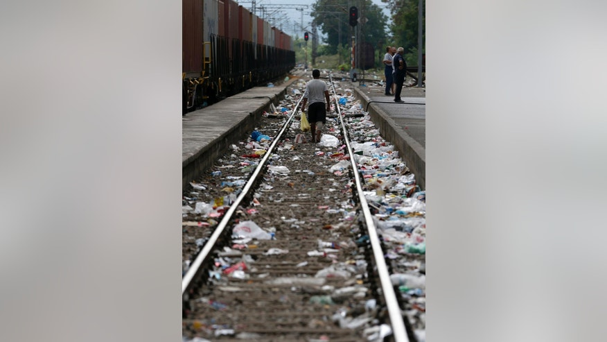 A man walks along the litter strewn  railway tracks at the railway station in the southern Macedonian town of Gevgelija, Thursday, Aug. 20, 2015. Macedonian  police  stepped up the security at the border with Greece apparently trying to stem recent surge of migrants who are coming from Greece. (AP Photo/Darko Vojinovic)