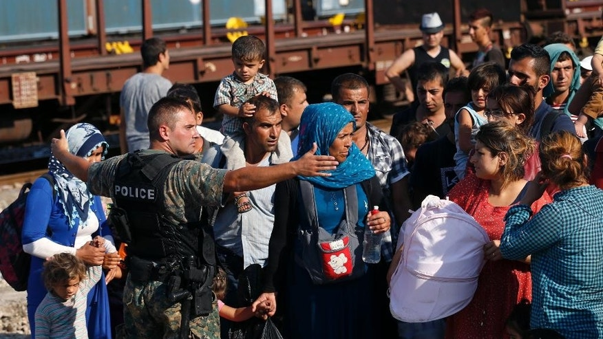 In this Wednesday, Aug. 19, 2015, photo, Amina Asmani, second from right, watches a police officer secure the railway tracks before a train that would take the migrants towards Serbia enters the railway station, in the southern Macedonian town of Gevgelija. Thousands of migrants from Syria, Iraq, Afghanistan and other countries have been registered passing through the impoverished Balkan country over the past month, double than the month before. (AP Photo/Darko Vojinovic)
