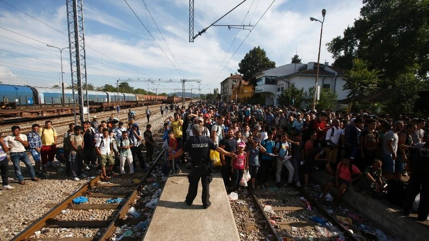 In this Wednesday, Aug. 19, 2015, photo, a police officer, center, secures the railway tracks before a train that would take the migrants towards Serbia enters the railway station, in the southern Macedonian town of Gevgelija. A record number of migrants from countries like Syria, Iraq, and Afghanistan have been registered passing through the impoverished Balkan country over the past month, double than the month before. (AP Photo/Darko Vojinovic)