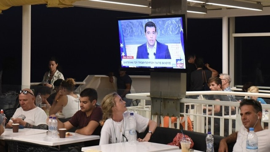 Aug. 20, 2015: A tourist watches Greek Prime Minister Alexis Tsipras, deliver a televised address to the nation, on a television screen aboard a ferry traveling in the Aegean sea, near Syros island. (AP Photo/Giannis Papanikos)