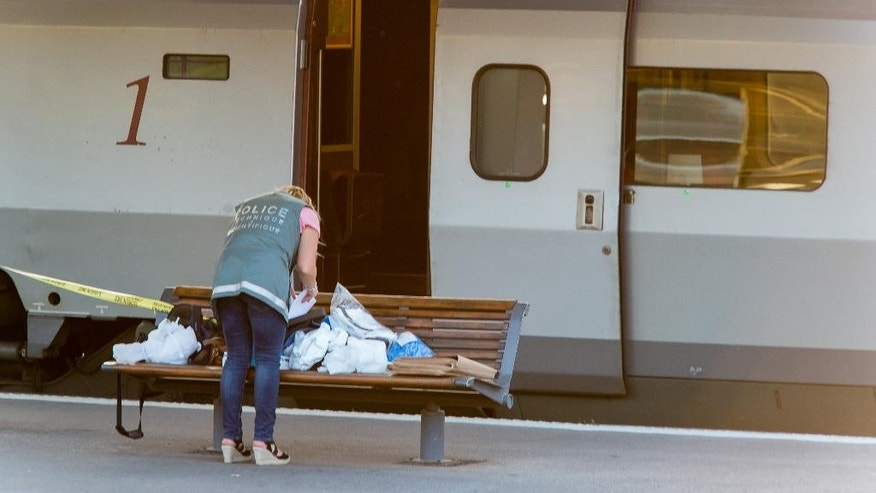 A police officer works on a platform near a Thalys train of French national railway operator, SNCF, at the main train station in Arras, northern France, after a gunman opened fire injuring three passengers, Friday, Aug. 21, 2015. A spokesman for France's interior ministry says three people were wounded in a shooting on a high-speed train traveling from Amsterdam to Paris Friday. Speaking on French television BFM, Pierre-Henri Brandet says a suspect is in custody and the train has been evacuated in Arras, 115 miles (185 kilometers) north of Paris, where the train stopped after the attack. (AP Photo)