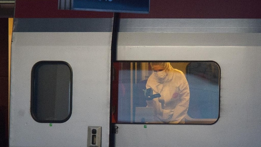 ALTERNATE CROP TO REB103 - A police officer videos the crime scene inside a Thalys train at Arras train station, northern France, Friday, Aug. 21, 2015. A gunman opened fire with an automatic weapon on a high-speed train traveling from Amsterdam to Paris Friday, wounding three people before being subdued by two American passengers, officials said. French Interior Minister Bernard Cazeneuve, speaking in Arras in northern France where the suspected was detained, said one of the Americans was hospitalized with serious wounds. (AP Photo)
