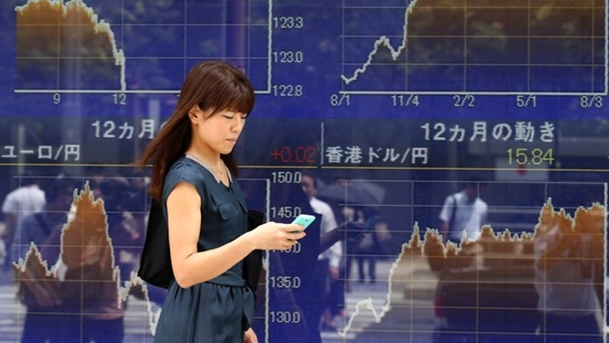 Aug. 21, 2015: A woman using a smartphone walks by an electronic stock board of a securities firm in Tokyo. Tokyo's Nikkei 225 plunged 2 percent in the morning session as Asian stocks fell further Friday after a survey showed Chinese manufacturing weakened this month. (AP Photo/Koji Sasahara)