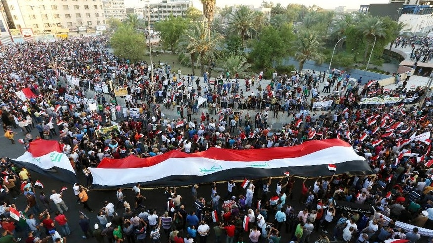 Protesters chant in support of Iraqi Prime Minister Haider al-Abadi as they carry a large national flag during a demonstration in Tahrir Square in Baghdad, Iraq, Friday, Aug. 21, 2015. Thousands rallied in Iraq's capital and a string of other cities to press demands for reforms, better services and an end to corruption. (AP Photo/Khalid Mohammed)