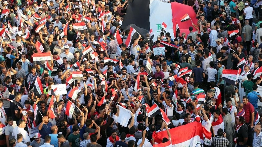 Protesters chant in support of Iraqi Prime Minister Haider al-Abadi as they carry national flags during a demonstration in Tahrir Square in Baghdad, Iraq, Friday, Aug. 21, 2015. Thousands rallied in Iraq's capital and a string of other cities to press demands for reforms, better services and an end to corruption. (AP Photo/Khalid Mohammed)
