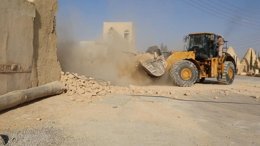 This picture released late Thursday, Aug. 20, 2015, by an ISIS-affiliated website, shows a bulldozer destroying the Saint Eliane Monastery near the town of Qaryatain which ISIS militants captured in early August, in Homs province, Syria. A priest and activists say ISIS demolished an ancient monastery in central Syria.