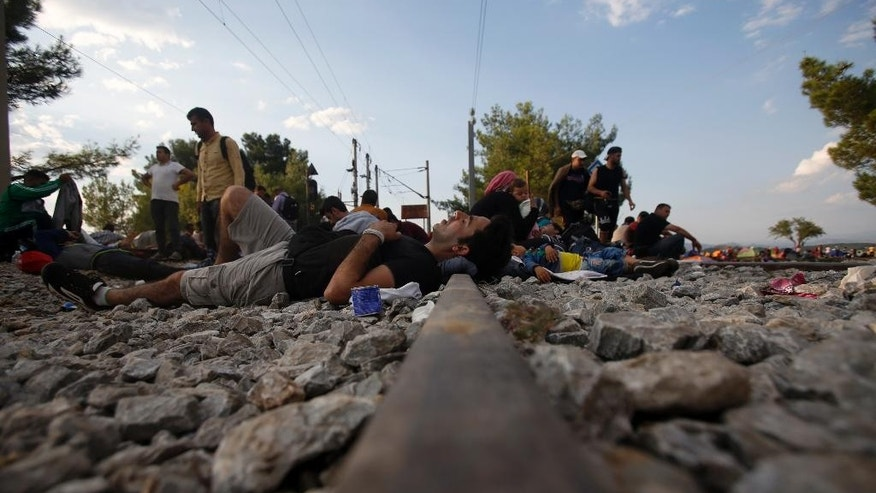 Migrants rest near the border train station of Idomeni, northern Greece, as they wait to be allowed by the Macedonian police to cross the border from Greece to Macedonia, Thursday, Aug. 20, 2015. Thousands of migrants were stranded Thursday on no-man's land between Macedonia and Greece near the Macedonian town of Gevgelija, from where they planned to catch trains that would take them to the Serbian border on their way to EU-member Hungary. (AP Photo/Darko Vojinovic)