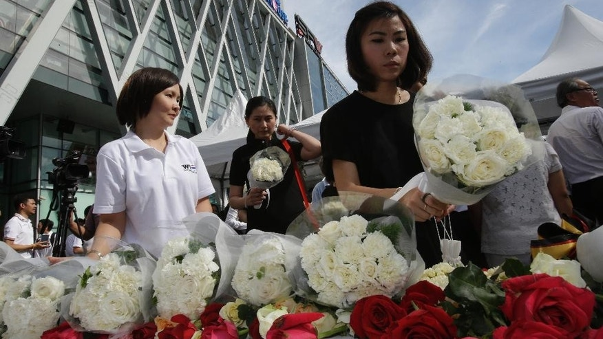 People leave flowers at a shopping plaza across from the Erawan Shrine at Rajprasong intersection, the scene of Monday's bombing, for a multi-denominational religious service for victims in Bangkok, Thailand, Friday, Aug. 21, 2015. Religious ceremonies were held to honor the victims of the deadly bombing at a Bangkok shrine four days ago. (AP Photo/Sakchai Lalit)