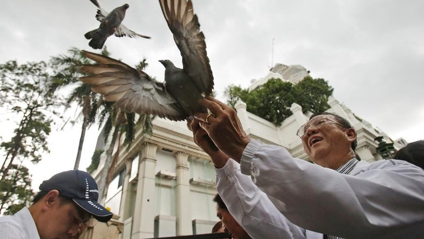 Doves are released for peace at the Erawan Shrine at Rajprasong intersection, the scene of Monday's bombing, in Bangkok, Thailand, Friday, Aug. 21, 2015. Somber horns sounded Friday at the site of Bangkok's deadly bomb blast as officials joined a multi-religious ceremony for victims of this week's attack, the latest effort to show that the bustling capital was respectfully, if cautiously, moving on.(AP Photo/Sakchai Lalit)