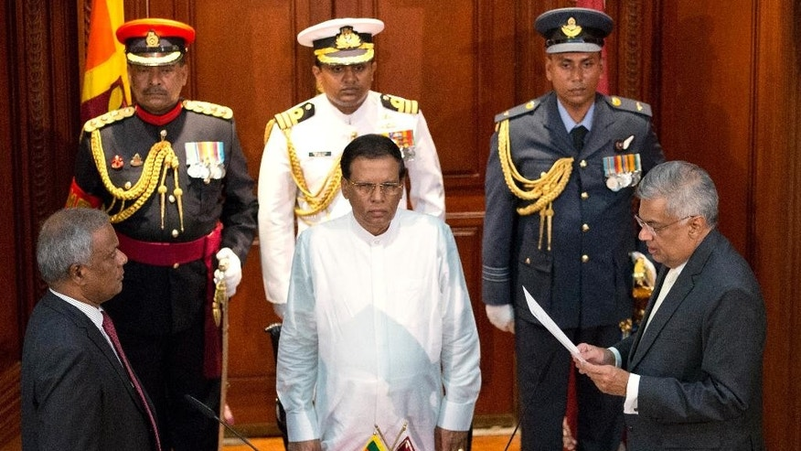 Ranil Wickremesinghe, right, takes oath as Sri Lanka's prime minister in front Sri Lanka's president Maithripala Sirisena, center, in Colombo, Sri Lanka, Friday, Aug. 21, 2015. Wickremesinghe's victory in Monday's election thwarted a political comeback bid by the country's former strongman president, Mahinda Rajapaksa, seven months after he lost his presidential re-election bid. (AP Photo/Gemunu Amarasinghe)