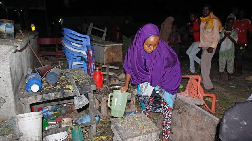 A woman gathers her destroyed belongings  in Mogadishu, Somalia, Saturday, Aug. 22, 2015. Four people were killed when a parked car exploded near a bus station in northern Mogadishu, said Capt. Mohamed Hussein. The attack in the capital bore the hallmarks of al-Shabab. (AP Photo/Farah Abdi Warsameh)