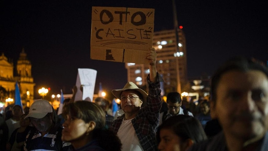 "A protester holds a sign that reads in Spanish ""Otto, you're down,"" referring to President Otto Perez Molina, after the arrest of his former Vice President Roxana Baldetti, who was arrested in connection with a corruption scandal, in the Central Park of Guatemala City, Friday, Aug. 21, 2015. Baldetti was detained Friday in connection with a customs corruption scandal that led to her resignation, and prosecutors announced they are also seeking to investigate the president in the matter. (AP Photo/Luis Soto)"