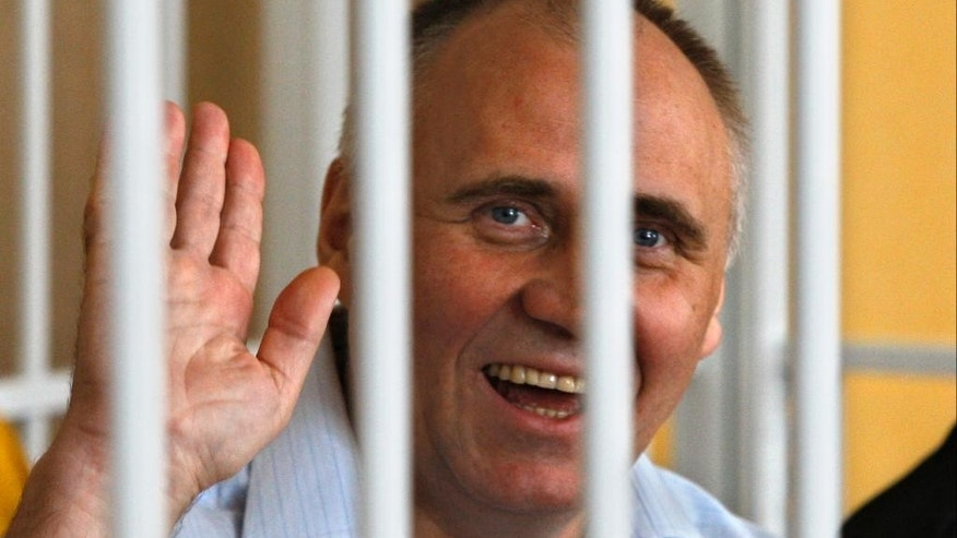 "FILE - In this Thursday, May 26, 2011 file photo, former opposition presidential candidate Nikolai Statkevich waves as he sits in a cage during a court session in Minsk, Belarus. The authoritarian president of Belarus on Saturday pardoned all six political prisoners in the former Soviet republic, including Statkevich, a former opposition presidential candidate. President Alexander Lukashenko's office said the president, ""proceeding from the principle of humanism,"" decided Saturday, Aug. 22, 2015 to pardon and release Statkevich and five others who are considered to be political prisoners. (AP Photo/Sergei Grits, file)"