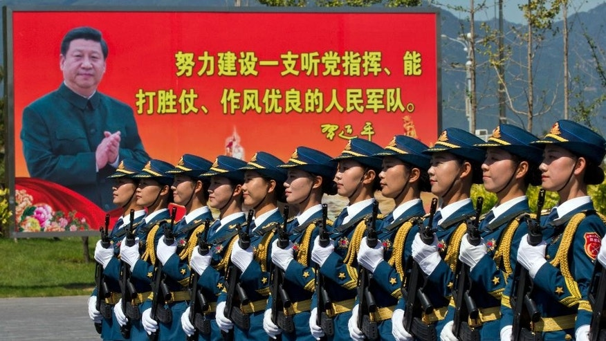 "Chinese female troops practice marching near a billboard showing Chinese President Xi Jinping and the slogan ""Strive to build a People's Liberation Army that obeys the Party, Wins the war and has outstanding work style"" at a camp on the outskirts of Beijing, Saturday, Aug. 22, 2015. China is ramping up publicity for its upcoming World War II military parade that will feature 12,000 soldiers and 500 pieces of military equipment, but officials still aren't saying which other countries are taking part in the spectacle. (AP Photo/Ng Han Guan)"