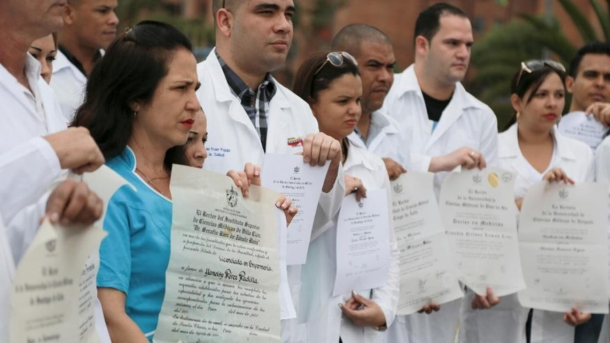 Yaneisy Perez, left, and fellow Cuban doctors, show their diplomas during a protest to draw attention to their plight to get U.S. visas at the Banderas square in Bogota, Colombia, Saturday, Aug. 22, 2015. Dozens of health workers who defected while serving on aid missions in Venezuela fled to Bogota expecting to swiftly get visas to the United States under the 2006 Cuban Medical Professional Parole Program, designed to help Cuban medical mission deserters find refuge in the U.S., but many complain they have been waiting for months without a response. (AP Photo/Ricardo Mazalan)