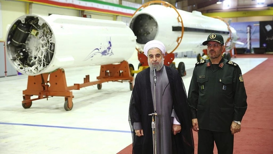 In this photo released by the official website of the office of the Iranian Presidency on Saturday, Aug. 22, 2015, Iran's President Hassan Rouhani, left, briefs the media as Defense Minister Hossein Dehghan listens after unveiling the surface-to-surface Fateh-313, or Conqueror, missile in a ceremony marking Defense Industry Day, Iran.  Iran unveiled a short-range solid fuel ballistic missile Saturday, an upgraded version that the government says can more accurately pinpoint targets.  (Iranian Presidency Office via AP)