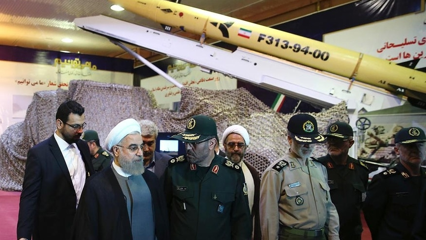 In this photo released by the official website of the office of the Iranian Presidency on Saturday, Aug. 22, 2015, Iran's President Hassan Rouhani, second left, speaks with Defense Minister Hossein Dehghan after unveiling the surface-to-surface Fateh-313, or Conqueror, missile in a ceremony marking Defense Industry Day, Iran. Iran unveiled a short-range solid fuel ballistic missile Saturday, an upgraded version that the government says can more accurately pinpoint targets. (Iranian Presidency Office via AP)