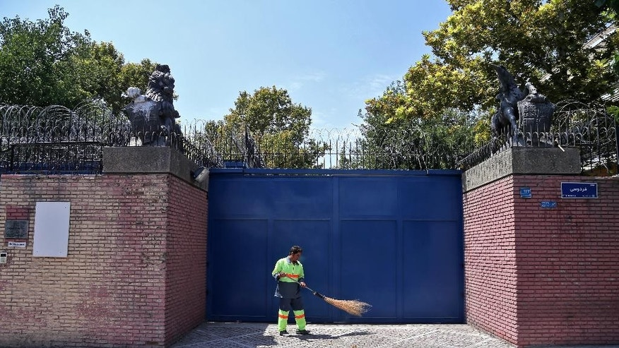 An Iranian street sweeper cleans in front of the British Embassy in Tehran, Iran, Saturday, Aug. 22, 2015. IIranian state-run media has reported the British Embassy in Tehran will reopen Sunday. The embassy has been closed for almost four years after hard-liners protesting the imposition of international sanctions over Iran's contested nuclear program stormed it in November 2011. (AP Photo/Ebrahim Noroozi)