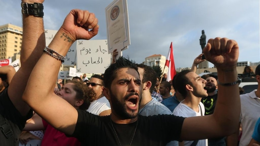 Lebanese activists chant slogans during a protest against the ongoing trash crisis, in downtown Beirut, Lebanon, Saturday, Aug. 22, 2015. Police have unleashed tear gas and water cannons on thousands of Lebanese demonstrating in downtown Beirut against government corruption and political dysfunction that has left garbage accumulating in the streets in suburbs of the capital for over a month. (AP Photo/Bilal Hussein)